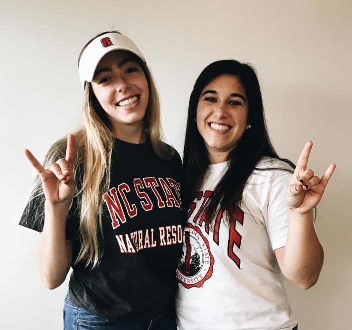 Current and future classmates Cassidy Grosz  and Alyssa Tangradi throw wolf signs to their future wolfpack classmates.