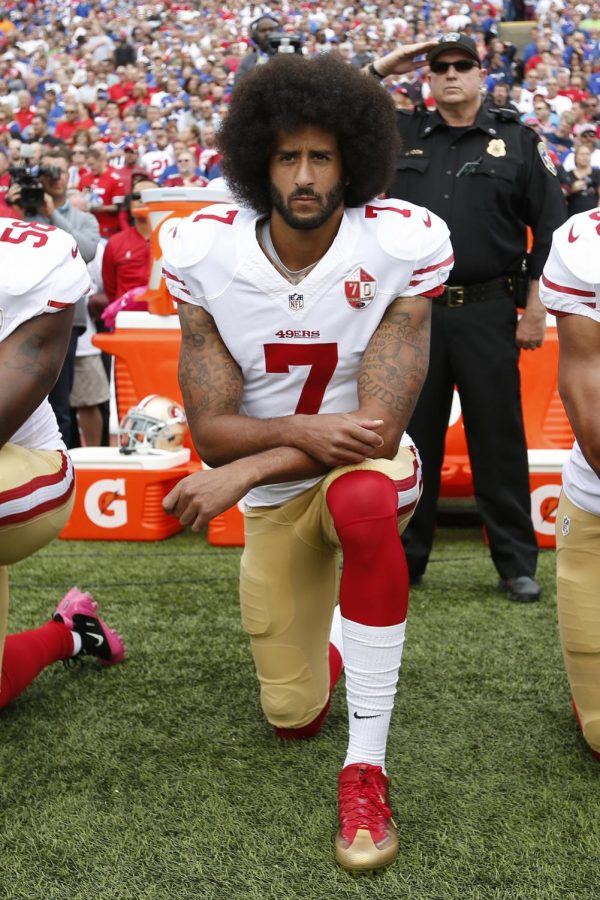 San Francisco 49er's quarterback Colin Kaepernick protests during the National Anthem.