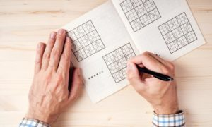 Top view of male hands solving sudoku puzzle on wooden office desk; Shutterstock ID 432200938; Purchase Order: -