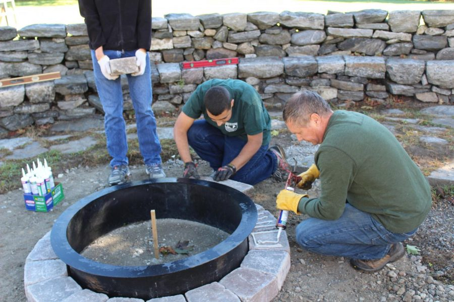 Working on his firepit at the Elk's Club , Matt Scipioni represents the hard work and dedication necessary to be an Eagle Scout, as also embodied by fellow Eagle scout Peter Arnold.