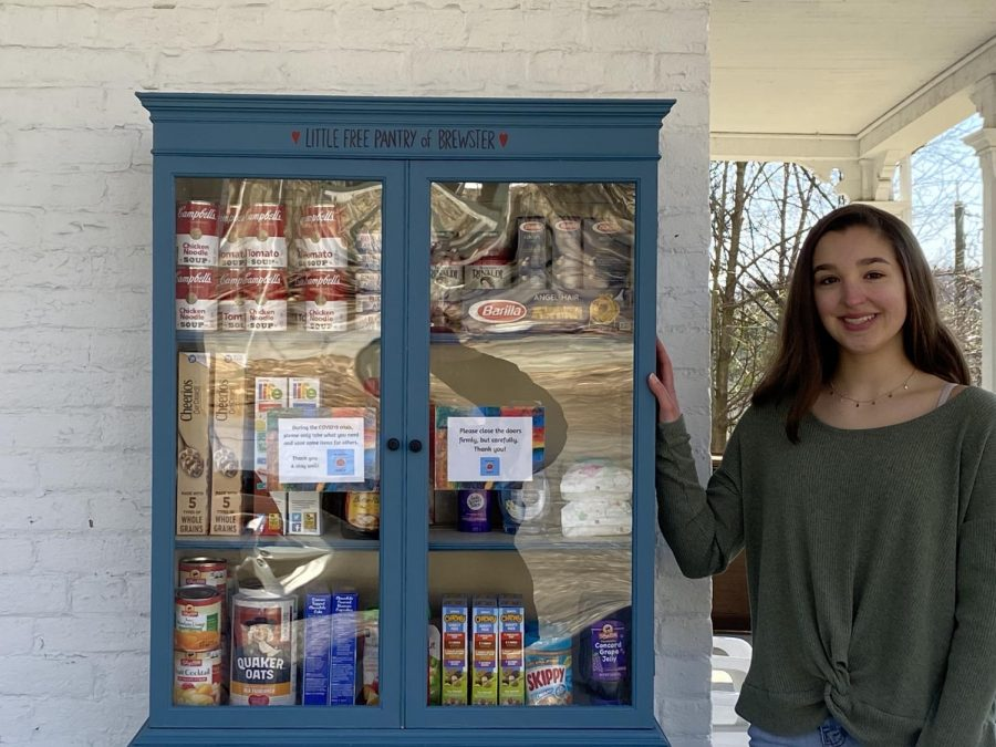 Junior Nora Paladino proudly stands before her Little Free Food Pantry, ready to bring the community together and meet the needs of its members.